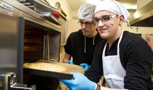Unterricht in der Schulküche: Absolventen des Berufsgrundschuljahres schieben einen Teig in den Ofen. Foto: SMMP/Bock