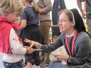 """""""Auch Du gehörst dazu"""" - Sr. Maria Elisabeth Goldmann spricht am Stand der Deutschen Ordensobernkonferenz (DOK) mit einem Kind über die Kirche. Foto: SMMP/Meilwes"""