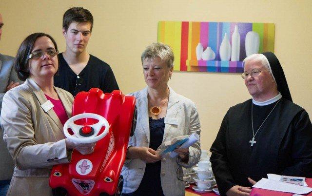 """Andrea Starkgraff überreicht Ursula Jenke im Beisein von Generaloberin Sr. Aloisia Höing einen neuen """"Dienstwagen"""" für das Mutter-Kind-Wohnen im Julie-Postel-Haus. Der SMMP-Aufkleber ist natürlich schon drauf. Foto: SMMP/Beer"""