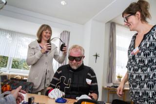 Mit Gewichten am Körper, Handschuhen und einer Brille, die den Grauen Star simuliert, versucht sich der Probant Werner Klenner an feinmotorischen Aufgaben. Foto: SMMP/Bock