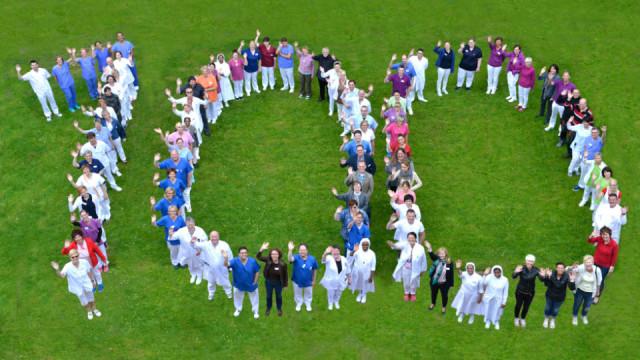 Mitarbeiterinnen und Mitarbeiter des Gertrudis-Hospitals in Herten-Westerholt stellen sich zu einer großen 100 zusammen. Foto: KKRN / Günther Schmidt