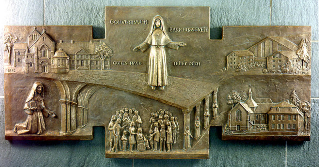 Dieses Relief von Hubert Hartmann zeigt Placida Viel auf einer Brücke zwischen St. Sauveur-le-Vicomte und Heiligenstadt. Brückenpfeiler sind die vier Lehrerinnen, mit denen sie im Eichsfeld die erste deutsche Niederlassung der Gemeinschaft gründete.