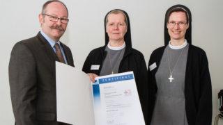 Die Leiterinnen der Ergotherapeutischen Praxen, Sr. Maria Gabriela Franke (m.) und Sr. Mirjam Grüßner (r.) erhalten 2013 von der Zertifizierungsgesellschaft DQS das Zertifikat nach DIN ISO 9001:2008. Foto: SMMP/Bock