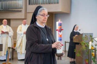 Schwester Laetitia Müller bringt bei der Gabenbereitung auch eine Kerze zum Altar. Foto: SMMP/Ulrich Bock