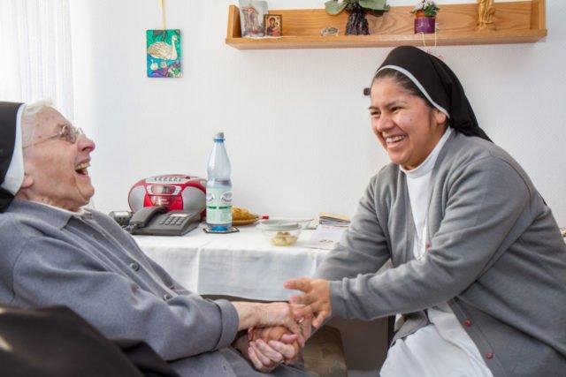Schwester Betty Castillo Barja half während ihres Auslandsjahres in Deutschland im Pfelegebereich der Schwestern im Bergkloster Bestwig mit. Hier lacht sie mit Schwester Hermine Schneider. Foto: SMMP/Ulrich Bock