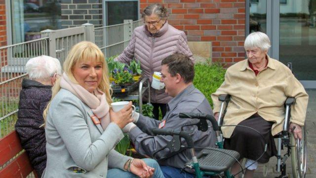Heimleiterin Astrid Thiele-Jerome (v.l.) und Pflegedienstleiter Alexander Hauffen (m.) pflanzen gemeinsam mit einigen Bewohnerinnen und Bewohnern die Hochbeete in dem großzügig angelegten Garten.